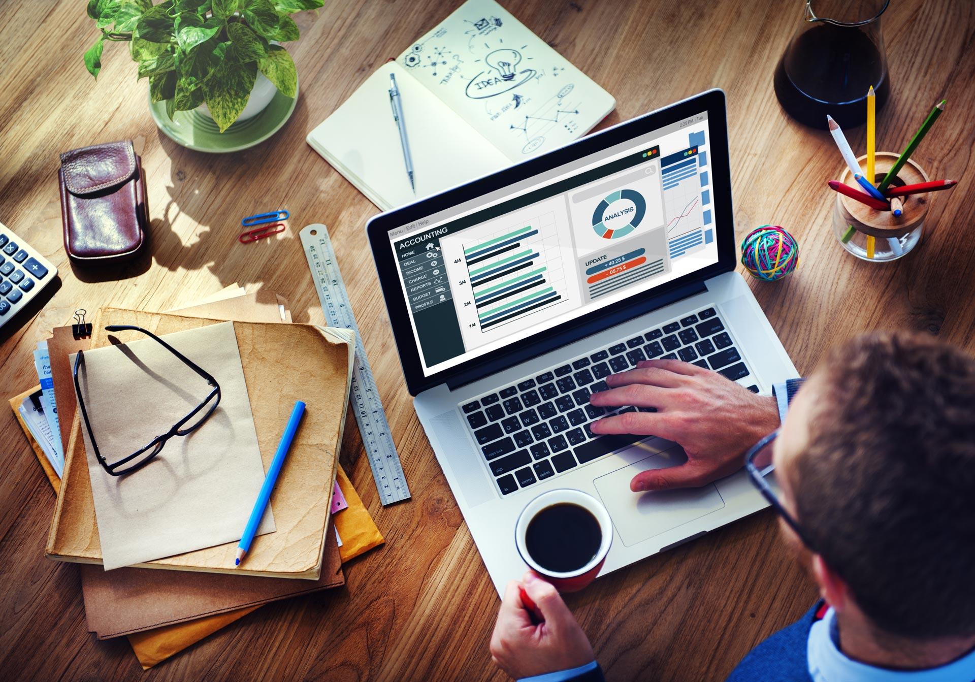 człowiek przy biurku z dokumentami, laptopem i kawą
